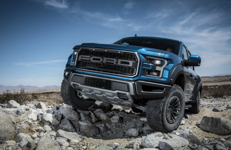 2019 Ford F-150 Raptor driving on rocks