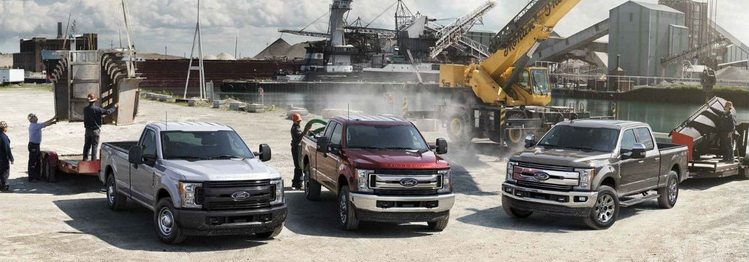 2019 Ford F-150 vs F-250 vs F-350 with image of the 2019 Ford Super Duty lineup at a busy work site